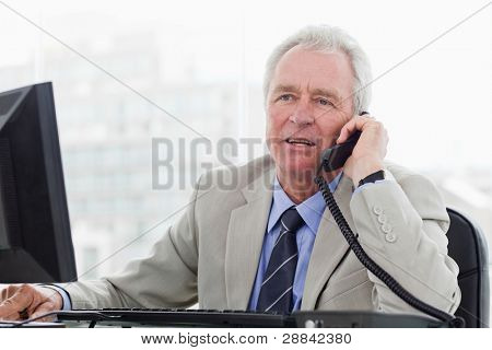 Senior manager on the phone in his office