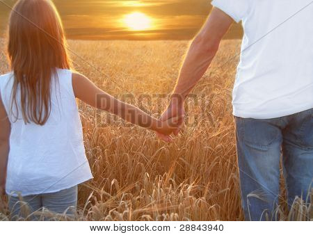 Father with his daughter at sunset in barley field