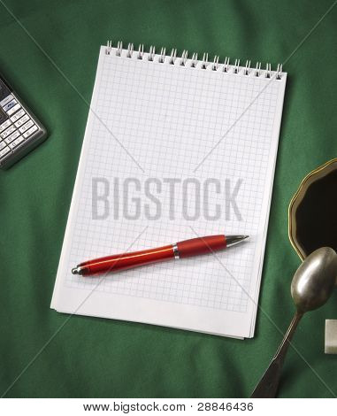 Diaries, red ballpoint pen, cup of coffee, mobile phone on green baize. High contrast