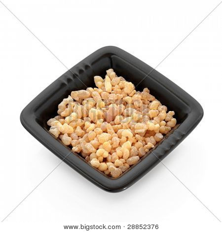 Myrrh resin in a black square dish isolated over white background.