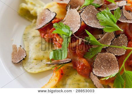 Freshly made italian ravioli pasta with slices of black truffle