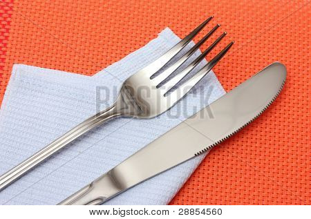 Fork and knife in a blue cloth on a red tablecloth
