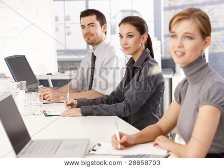 Young businessteam sitting at meeting table, listening presentation, writing notes.?
