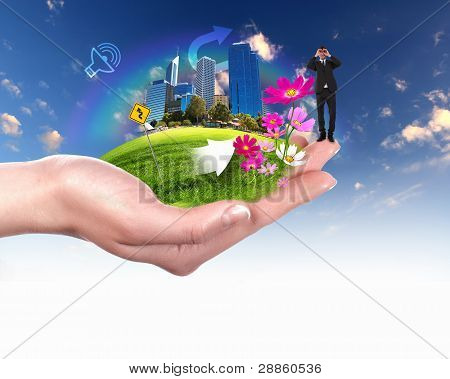 Human hand holding a green landscape