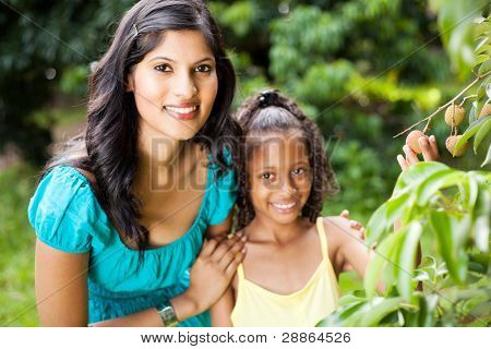 beautiful young mother and daughter in litchi orchard