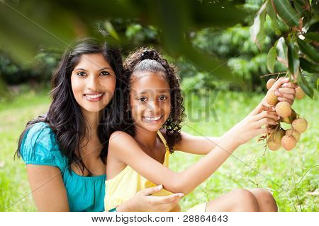 pretty young mother and daughter picking litchis