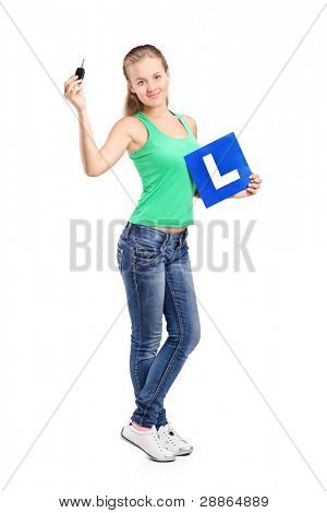 Full length portrait of a smiling teenager holding a L plate and car key isolated on white background