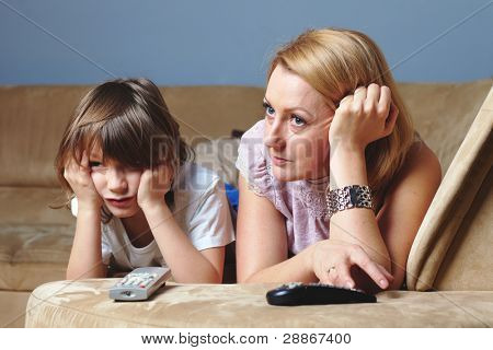 Young mother watch tv with her son, sad and serious face expression