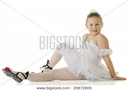 An elementary-aged ballerina resting gracefully in her dace costume.  On a white background.