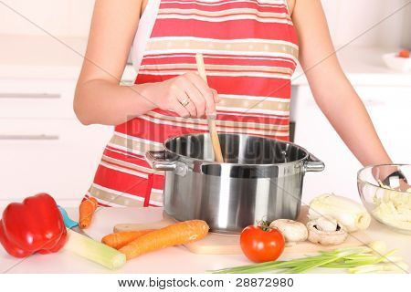 Una foto de un ama de casa preparando sopa en una olla en la cocina