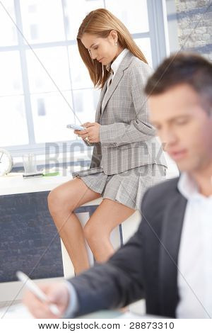 Sexy businesswoman in mini skirt texting in office, businessman working at desk.?