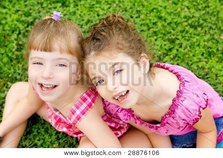 children girls laughing sitting on green grass park