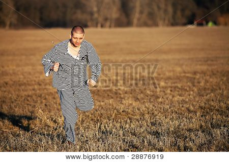 Evaded from a prison runing on a field