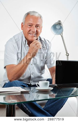 Portrait of smiling senior man sitting with laptop on table at home
