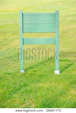 Wooden board for your message on green grass field
