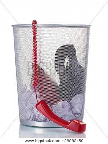 red phone,headphones and paper in metal trash bin isolated on white