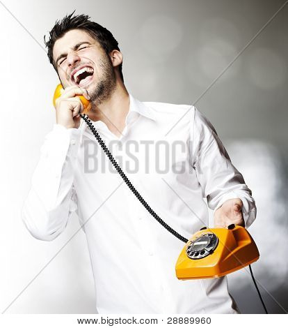 portrait of young man handsome laughing using a vintage telephone indoor