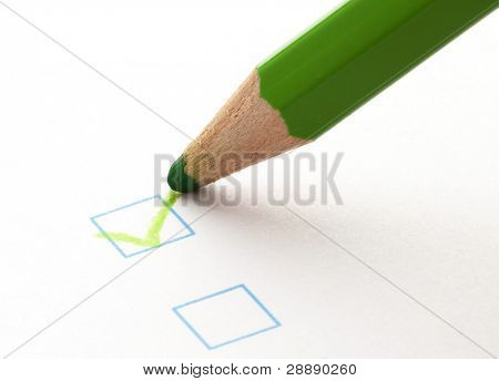 test check box and green crayon, closeup photo
