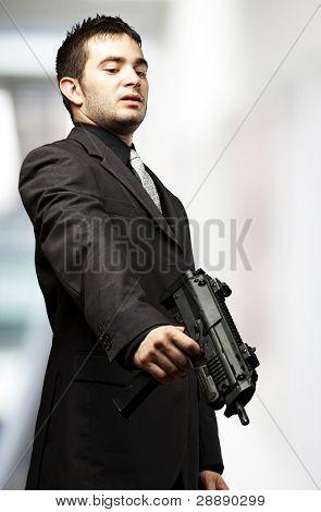 mafia man aiming down with gun against a indoor
