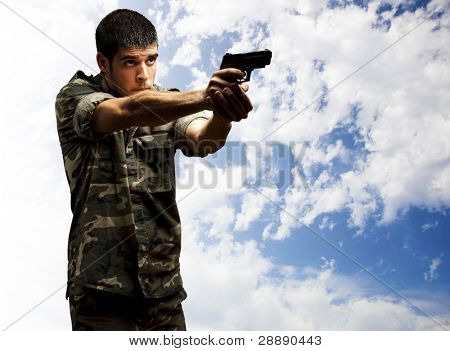 portrait of a young soldier aiming with pistol against a cloudy sky background