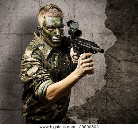 portrait of young soldier with jungle camouflage pointing with rifle against a grunge background