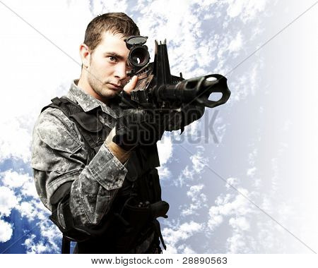 portrait of young soldier aiming with rifle against a blue sky background