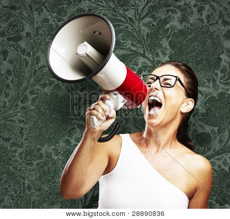 portrait of middle aged woman shouting using megaphone against a vintage wall