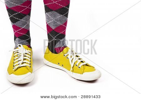 A flamboyant combination of flashy bright yellow sneakers paired up with pink plaid socks.