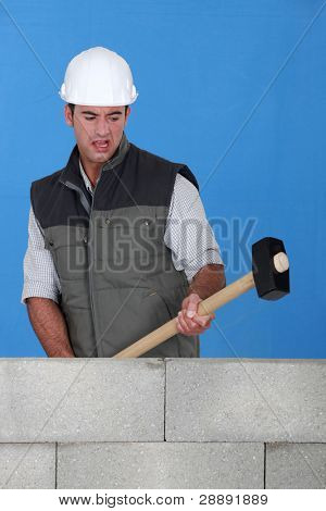 picture of bricklayer destroying wall with hammer
