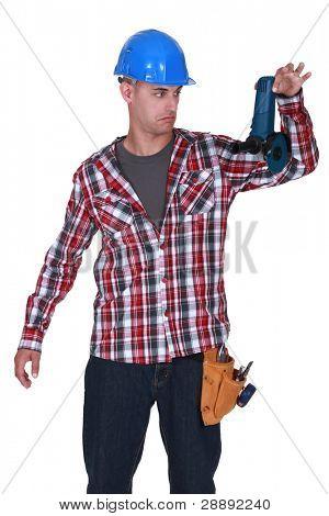 Man reluctantly holding angle grinder