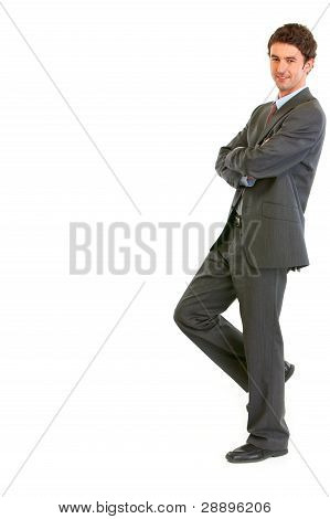 Smiling Modern Businessman Standing Back To Imaginary Wall