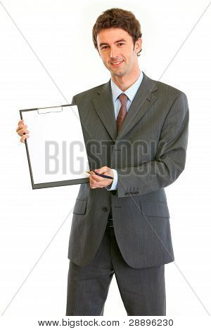 Smiling Modern Businessman Giving Clipboard For You To Sign