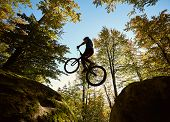 Young Male Biker Jumping On Trial Bicycle Between Two Big Boulders, Professional Rider Making Acroba poster