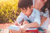Little Asian Boy And His Mother Reading Tale Story Books At Meadow Field. Mother And Son Learning To poster