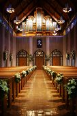 stock photo of church interior  - an image looking back down an isle of a church on a wedding day - JPG