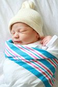 picture of sleeping baby  - Newborn baby asleep swaddled in hospital blanket and wearing a hat - JPG