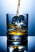 picture of alcoholic drinks  - Filling of a glass of whisky with ice - JPG