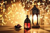 Ornamental Arabic Lanterns With Burning Candles. Glittering Golden Bokeh Lights. Plate With Date Fru poster
