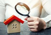 A Woman Is Holding A Magnifying Glass Over A Wooden House. Real Estate Appraiser. Assessment Of The  poster