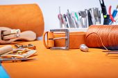 Leather Working Or Leather Craft. Orange Colored Or Tanned Leather On Leather Craftmans Work Desk .  poster