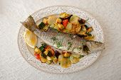 Fried sea bass with baked vegetables shot from above, Italian dish poster