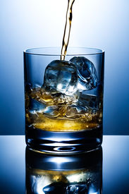 stock photo of alcoholic drinks  - Filling of a glass of whisky with ice - JPG