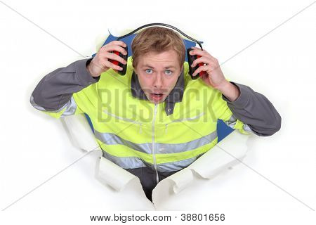 man with earmuffs emerging from poster