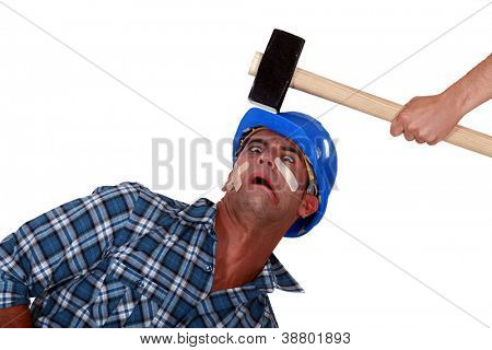 Man being hit over the head by hammer