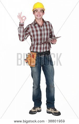 Builder holding clip-board making OK gesture