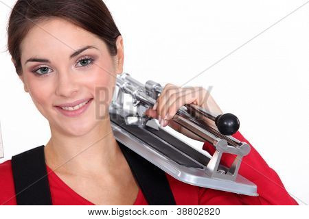 Woman holding tile cutting tool over shoulder