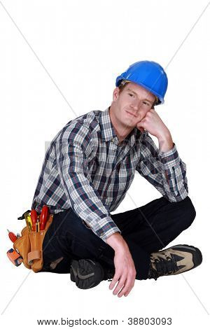 Dreamy tradesman sitting cross-legged