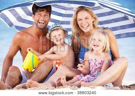 Family Sheltering From Sun Under Beach Umbrella