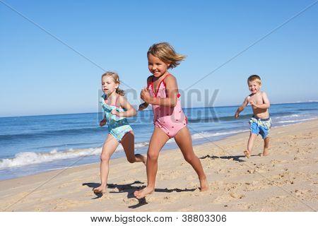 Three Children Running Along Beach