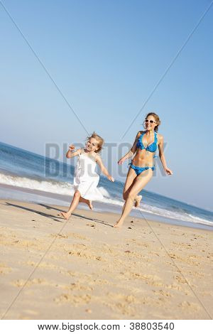 Mother And Daughter Running Along Beach